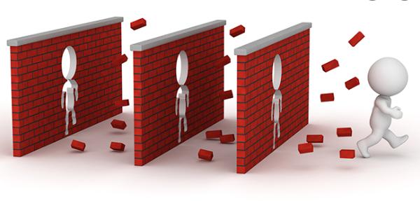 Man walking through brick wall barriers.